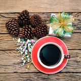 Christmas coffee cup. Coffee cup with gift box and pine corn on wooden board background stock image