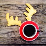 Christmas coffee cup. Coffee cup with reindeer headband on wooden board background Royalty Free Stock Images