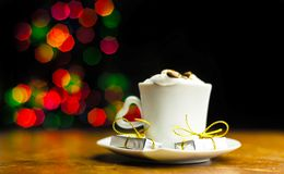 Christmas coffee with whipped cream and a small gift on the background bokeh lights, xmas stock photo