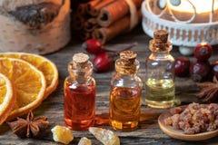 Christmas collection of essential oils with frankincense, myrrh, cinnamon, rose hips and orange slices. Christmas collection of essential oils with myrrh stock photo
