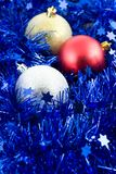 Christmas colored balls in blue tinsel Stock Photography