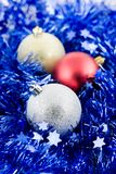 Christmas colored balls in blue tinsel Stock Photo