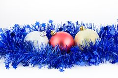 Christmas colored balls in blue tinsel top Royalty Free Stock Photos