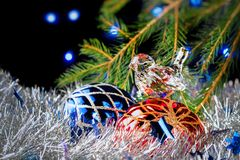 Christmas decorations lying in tinsel and fir branches on a dark background with blurred lights Royalty Free Stock Photos