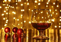 Christmas colorful balls and glass cognac or whiskey with defocused lights Royalty Free Stock Photos