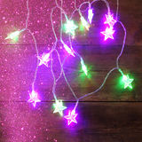 Christmas colorful garland lights on wooden rustic background. filtered image. Royalty Free Stock Photos