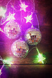 Christmas colorful gold garland lights and bauble on wooden rustic background. filtered image with glitter overlay. Stock Photography