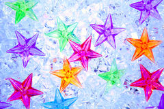 Christmas colorful stars on blue ice Stock Images