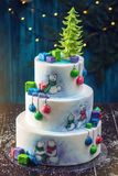 Christmas colorful three-Tiered cake decorated with drawings of Teddy bears, gift boxes and a green tree top Stock Photo