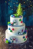 Christmas colorful three-Tiered cake decorated with drawings of Teddy bears, gift boxes and a green tree top Royalty Free Stock Photography