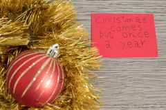Christmas comes but once a year write on a red paper with decorations stock photos