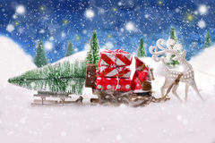 Christmas is coming. Christmas eve snowy night scene with white reindeer pulling santa`s sleighs with gifts and christmas tree royalty free stock image