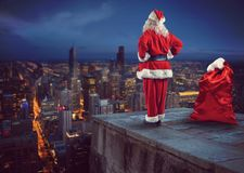 Santa Claus looks down on the city waiting to deliver the presents. Christmas is coming. Santa Claus on a roof view city royalty free stock photo