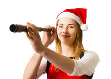 Christmas coming soon. Santa woman looking to the distance with monocular for the oncoming holiday season. Christmas coming soon Royalty Free Stock Images