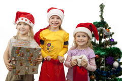 Christmas is coming up!. Three young little caucasian blond girls standing together near christmas tree holding gifts and smiling sincerely.isolated over white Stock Image