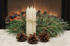 Advent. Christmas. White wax candles tied with thin jute cord, pine cones and pine branches on white lace napkin against the stock photos