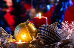 Christmas composition of Christmas balls and a brilliant decor with a candle. Greeting card with Merry Christmas. And a Happy New Year Stock Image