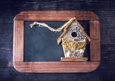 Christmas composition. Birdhouse on the chalkboard on wooden background Royalty Free Stock Photo