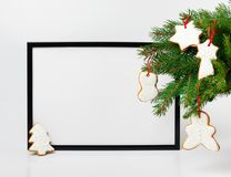 Christmas composition. Black frame and  branches christmas tree. With gingerbreads on white background. Front view, mock up, copy space, square, flat lay, for Stock Photos