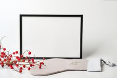 Christmas composition. Black frame and christmas sock with branc. Hes with red berries on white background. Front view, mock up, copy space, square, flat lay Stock Images