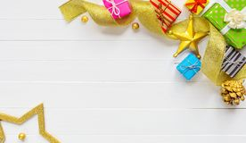 Christmas composition. Border made of christmas gifts and gold ribbon. Christmas border composition made of colorful gift boxes and gold ribbon on white wooden stock photo