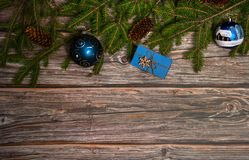 The border is made of spruce branches, cones, gift box and blue Christmas balls on a wooden background. Christmas, winter, New yea
