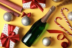 Christmas composition with bottle of champagne and gifts on color background. Top view stock images