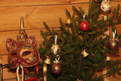 Christmas composition bouquet of tree with toys. And the Venice mask in a wooden house Stock Image