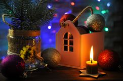Christmas composition with a burning candle, a house and Christmas decorations on a table. Against the background of colored garlands.n stock images