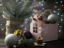 Christmas composition with a candle, a house and Christmas decorations on a table royalty free stock image