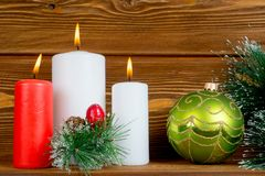 Christmas composition with candles pine brunch and ball. Christmas composition with candles pine brunch and bauble Royalty Free Stock Photo