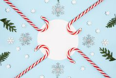 Christmas composition with candy cane, snow flakes and circle white paper blank on pastel blue background. View from the top stock photos