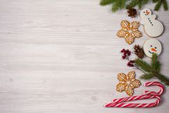 Christmas composition with candy canes, fir tree branches and ginger bread cookies. Winter holiday ornaments on white wooden background. Flat lay, top view stock images