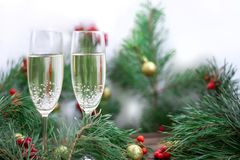 Christmas composition, champaign glasses, pine branches, red row. Christmas and New Year seasonal composition with pine tree branches, two glasses of champaign stock photos