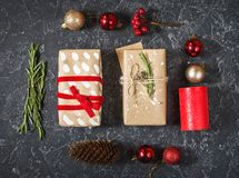Christmas composition. Christmas gifts, cone, toys on black stone background. Flat lay stock images