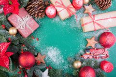 Christmas composition. Christmas green decorations, fir tree branches with toys gift boxes on green background. Flat lay. Top view, copy space stock photography