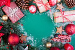 Christmas composition. Christmas green decorations, fir tree branches with toys gift boxes on green background. Flat lay. Top view, copy space stock images