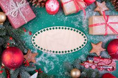 Christmas composition. Christmas green decorations, fir tree branches with toys gift boxes on green background. Flat lay. Top view, copy space stock photo