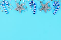 Christmas composition from Christmas tree toys. White decor on a blue background. Copy space, flat lay, top view. Christmas composition from Christmas tree toys Royalty Free Stock Photo