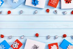 Christmas composition with copy space on light blue background. Red, blue and white gift boxes with bows and small royalty free stock image