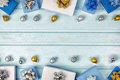 Christmas composition, copy space. Silver and gold Christmas balls, blue and white gift boxes decorated with bows. Festive layout on a light blue background royalty free stock image