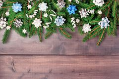 Christmas composition with copy space. Spruce branches decorated with decorative bows, spirals of ribbons and white snowflakes,. Laid out on a dark wooden stock image
