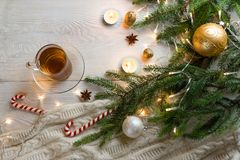 Cup of tea with christmas tree and candles. Christmas composition. Cup of hot fruit tea and Christmas candy canes on white wooden table. Candles and Christmas royalty free stock images