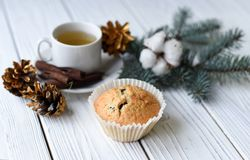 A Christmas composition with a cup of tea, homemade muffins, cones, fur twigs and cinnamon sticks. A festive Christmas composition with a cup of tea, homemade Stock Photography