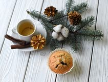 A Christmas composition with a cup of tea, homemade muffins, cones, fur twigs and cinnamon sticks. A festive Christmas composition with a cup of tea, homemade Stock Images