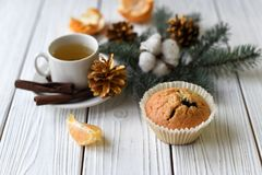 A Christmas composition with a cup of tea, homemade muffins, cones, fur twigs and cinnamon sticks. A festive Christmas composition with a cup of tea, homemade Stock Photos