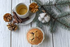 A Christmas composition with a cup of tea, homemade muffins, cones, fur twigs and cinnamon sticks. A festive Christmas composition with a cup of tea, homemade Royalty Free Stock Image