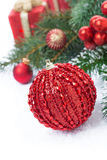 Christmas composition with decorative red ball, fir branches Stock Photos