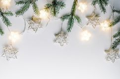 Christmas composition in Eco style. Fir branches, handmade stars and light bulbs on a white background. Stock Images