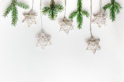 Christmas composition in Eco style. Fir branches and handmade stars on a white background. Stock Image